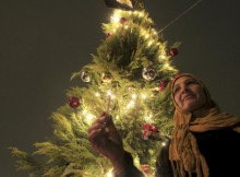 A Muslim woman lights a candle under a Chirstmas tree on Coptic Christmas eve at Tahrir Square in Cairo January 6, 2013. REUTERS/Mohamed Abd El Ghany (EGYPT  - Tags: RELIGION) - RTR3C627